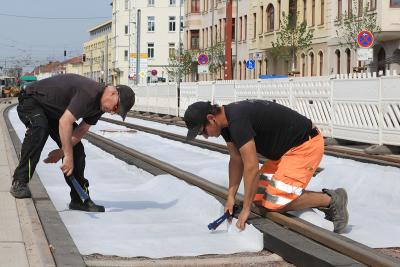 Die Bauarbeiter bringen das Flies ein, damit der Rollrasen verlegt werden kann. (Foto: Peter Gercke, 05/2020)